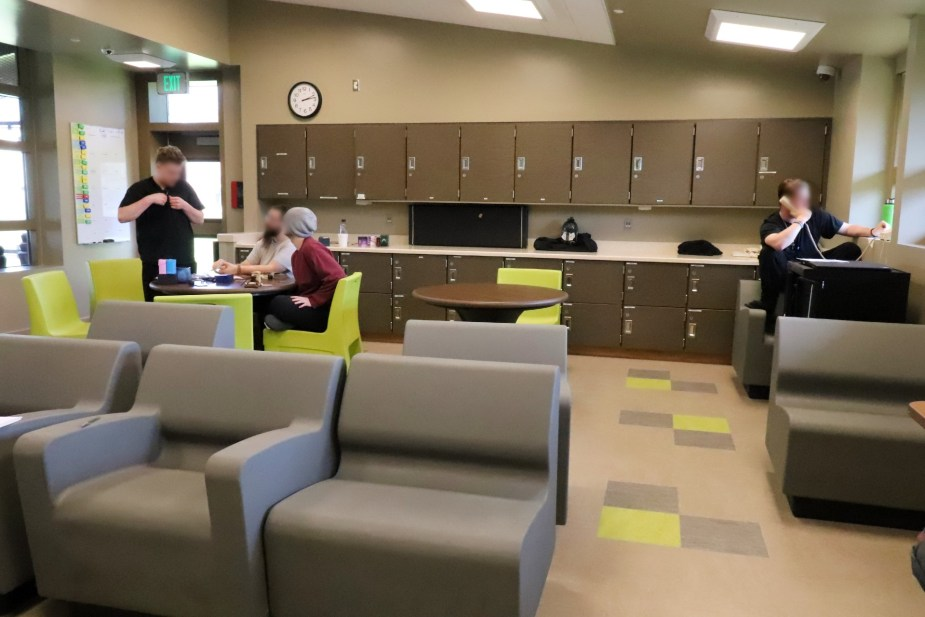 several young people sit at a table in a day room