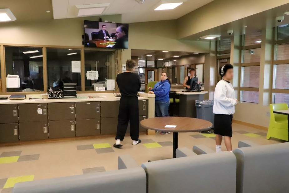staff and youth walk around in day room