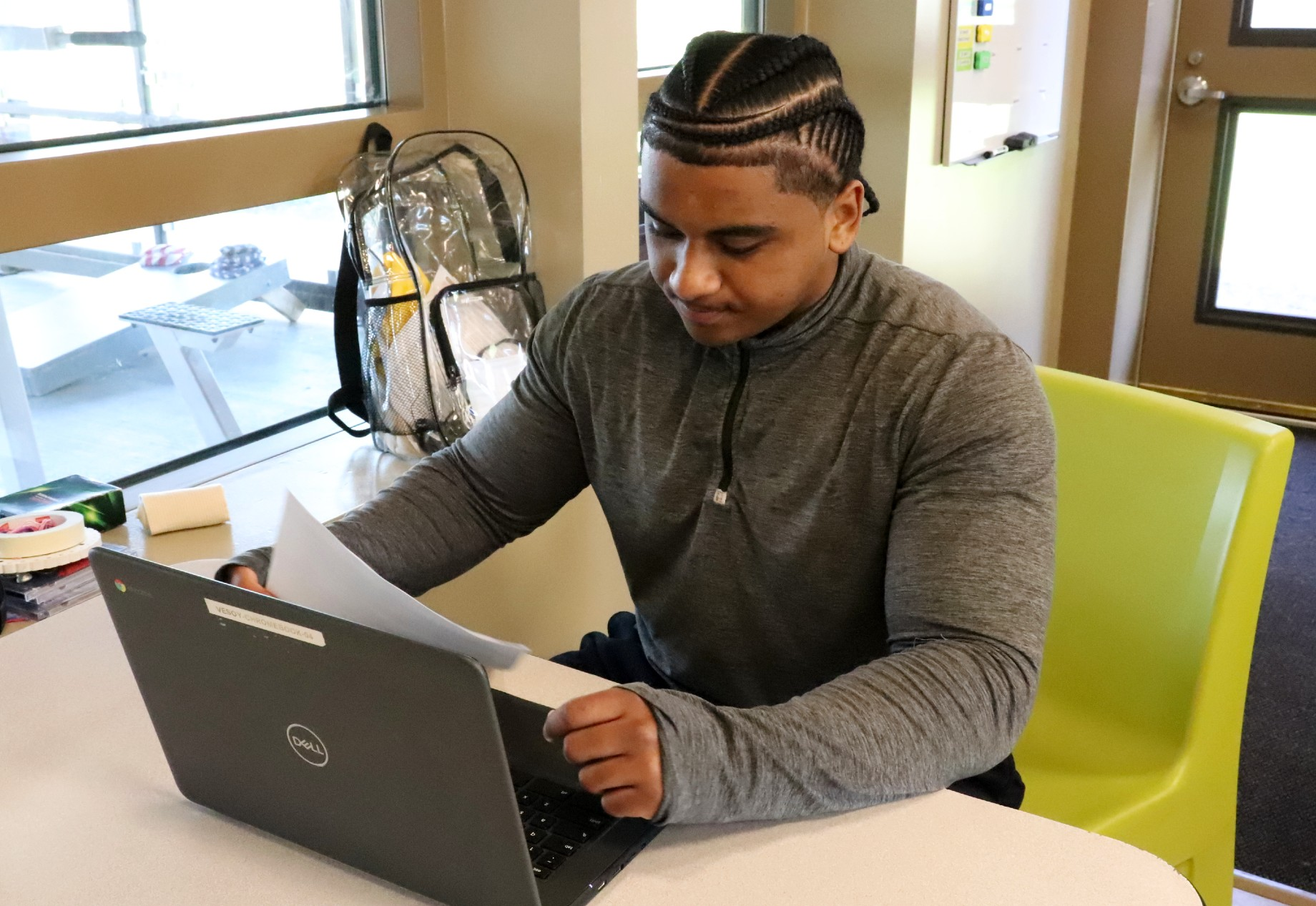a young men works at a laptop on a table