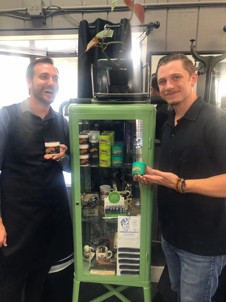 Two young men in a barber shop pose with a cabinet filled with hair products
