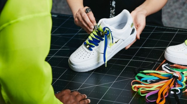 A sales assistant with a white sneaker and multicoloured shoelaces.