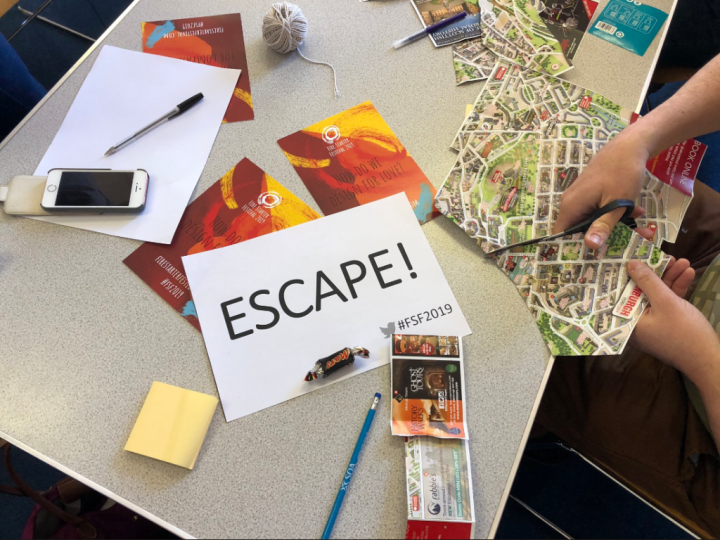 materials from the day with an A4 piece of paper reading 'ESCAPE!'