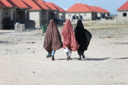 Women walk at the Bakassi camp for internally displaced people in Maiduguri, Nigeria, Nov. 29, 2016.