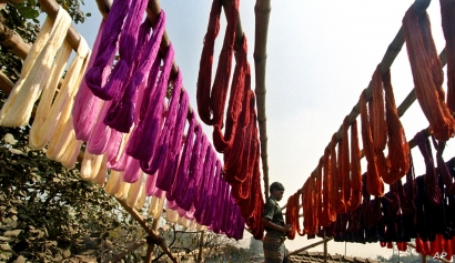 A daily paid laborer collects thread that has been dyed and left to dry in the sun, in Calcutta, India, Wednesday, June 1, 2005…