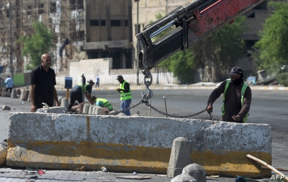 Iraqi municipal workers clean up Tayaran Square in central Baghdad on October 5, 2019 after a curfew was lifted.