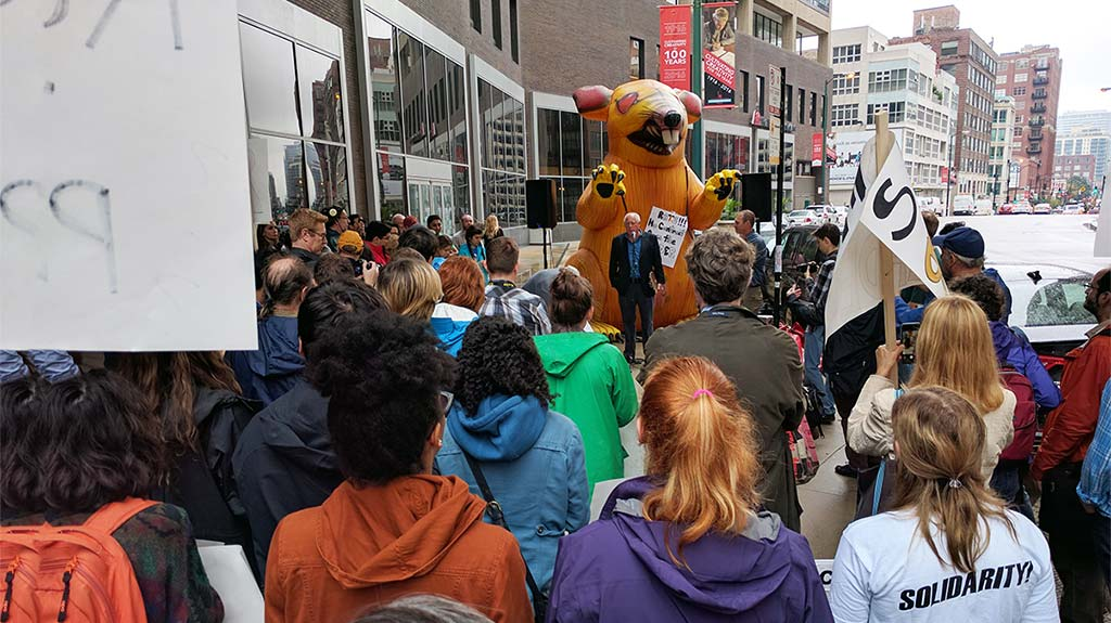 """Rally in Downtown Chicago. The photo is taken behind approximately ten rows of protesters with signs gathering around Former Illinois Governor Pat Quinn. Behind him is an orange inflatable rat with a sign reading """"RATS!!! No Contract from the Reader"""""""