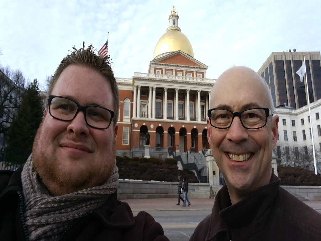 Douglas Rosenthal and Randy Hawes standing across the street from the Massachusetts State House's main enterance. Douglas is wearing a light brown scarf, brown jacket, and thick-frame black glasses to the right of Randy, who is wearing a dark brown jacket and thick-framed black glasses as well. The Massachusetts State House has a gold-leaf dome on top of a brown building with white molding and white pillars.