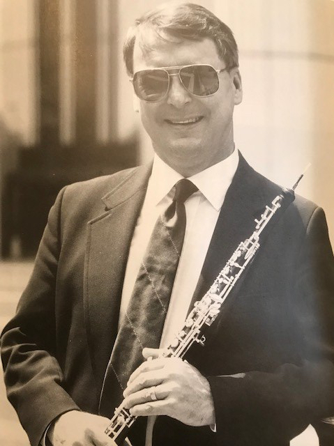 Joseph Robinson with sun glasses posing with his oboe