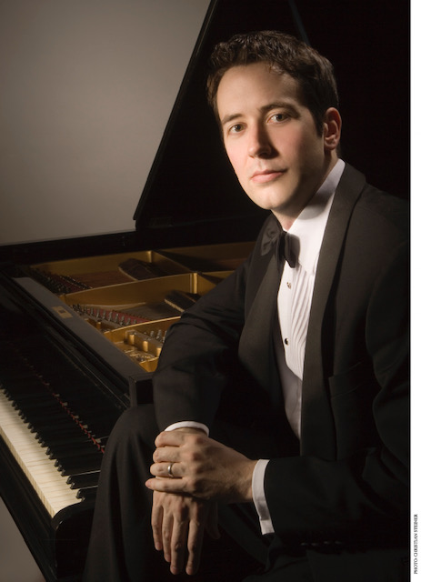 Philip Edward Fisher leaning against a grand piano in a tuxedo