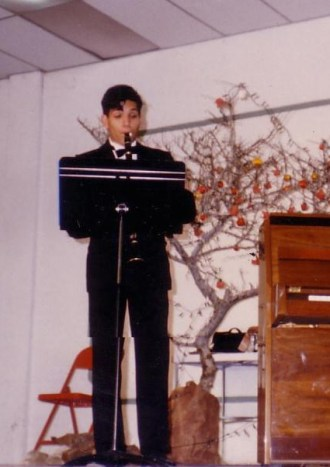 Ernesto Ramirez performing clarinet in a tuxedo while in college.