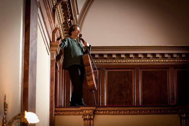 soloist Colin Carr standing with his cello in a concert hall.