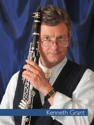 Kenneth Grant holding a clarinet by his face, wearing a vest