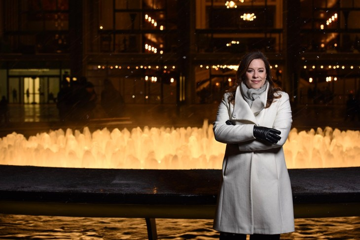 Jessica Phillips in a white coat at night standing in front of the fountains at Lincoln Center