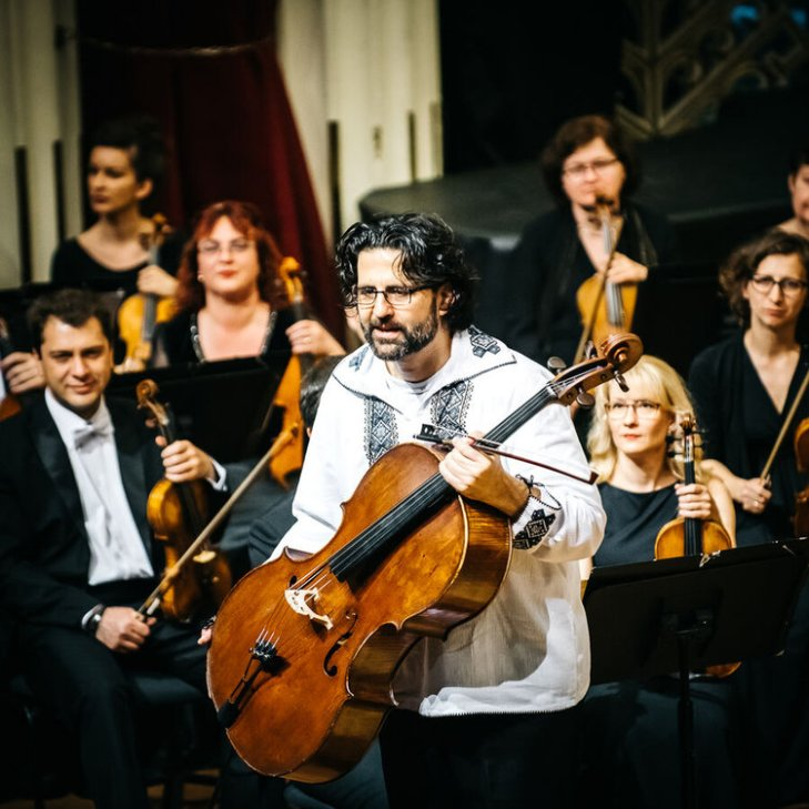 Cellist Amit Peled bowing before orchestra after a performance