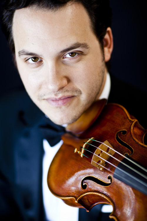close up picture of violinist Giora Schmidt in a tux holding his instrument under his chin