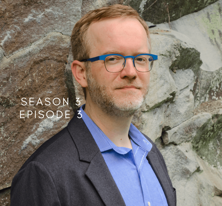 Jason Haaheim leaning against a stone wall with a suit and bright teal glasses