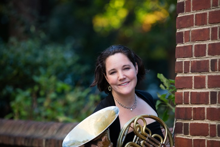 Jennifer Montone poses in concert black with her horn, next to a brick wall.