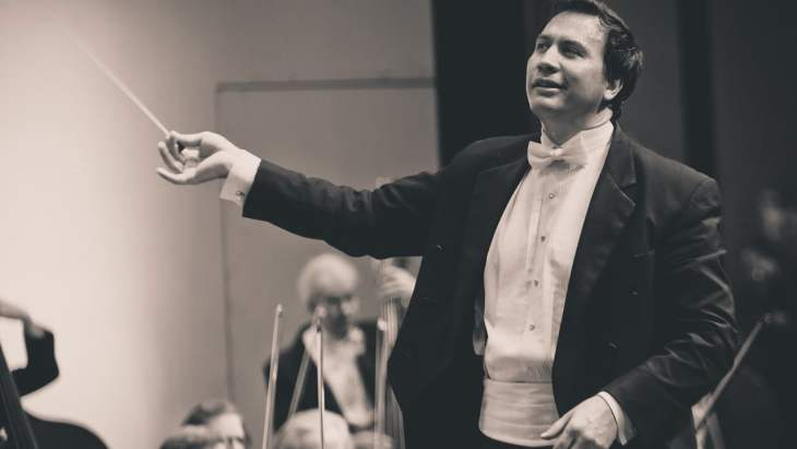 Black and White photo of Daniel Hege conducting holding the baton out in front of him.