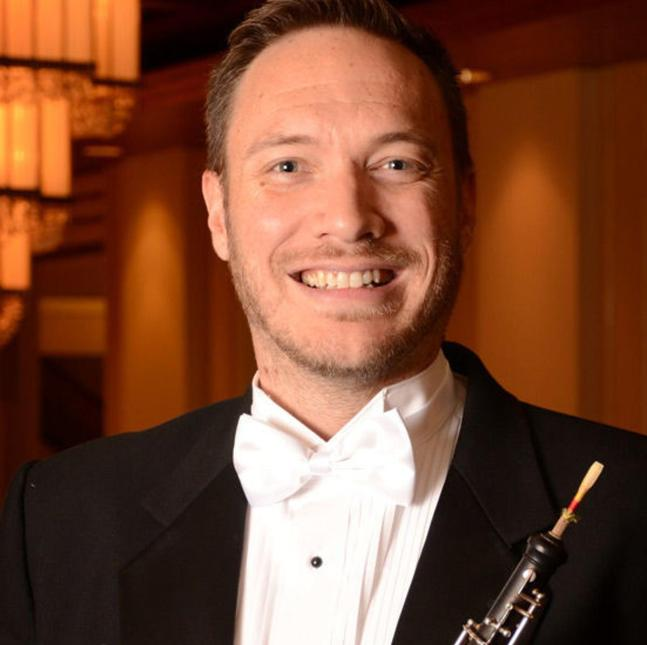 orchestral portrait of Andrew Parker, in white tie and tales, holding the oboe.