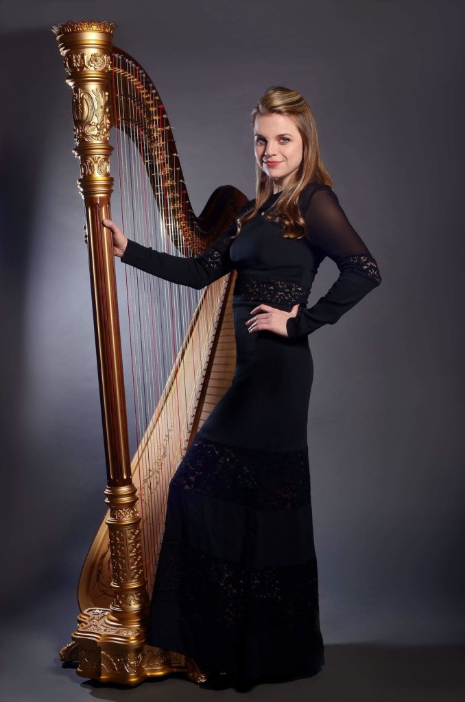 Grace Browning in concert black standing next to her harp in a professional headshot.