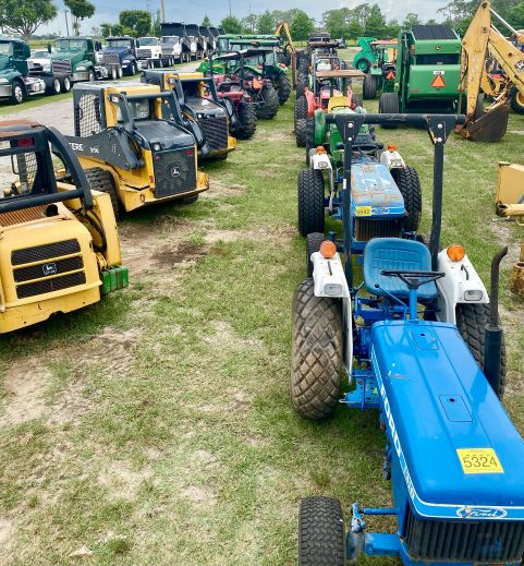Tractors and various equipment lined up in field
