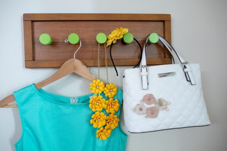 Blue dress, yellow flower necklace, yellow flower headband and white purse with pink flowers hanging from a wall-mounted coat rack.