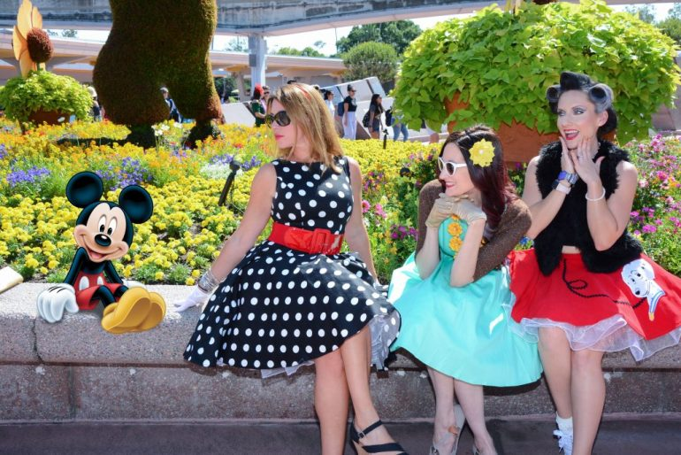 An animated Mickey Mouse is sitting on a ledge next to Theresa and two friends dressed up for Dapper Day.