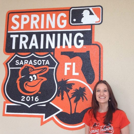 Theresa standing next to a the Orioles Spring Training 2016 logo painted on a wall.