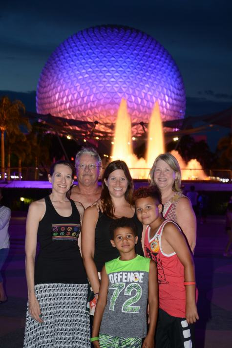Theresa with her two parents, sister, and two nephews standing together at night in front of Spaceship Earth at Epcot