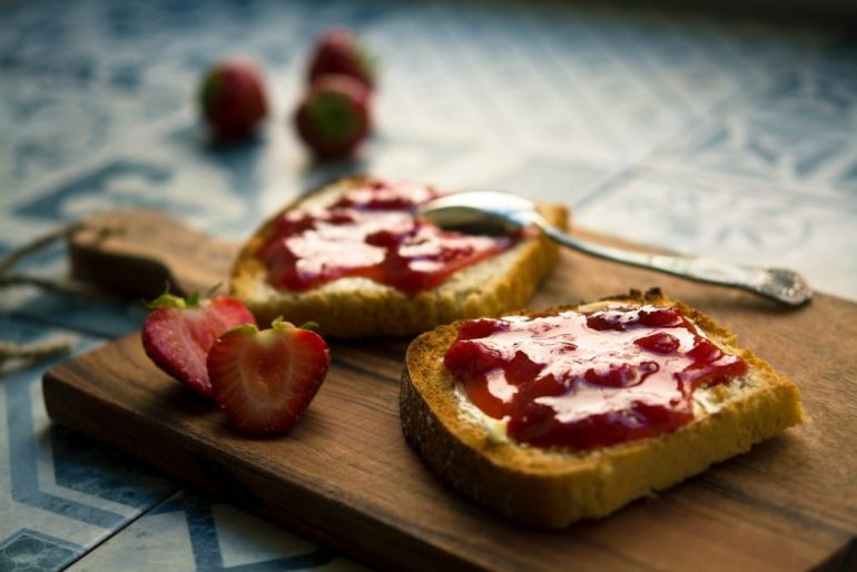 Two pieces of toast with jam on a wooden board next to sliced strawberries.