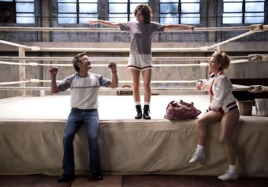 Scene from GLOW with three characters talking while hanging on and around a wrestling ring