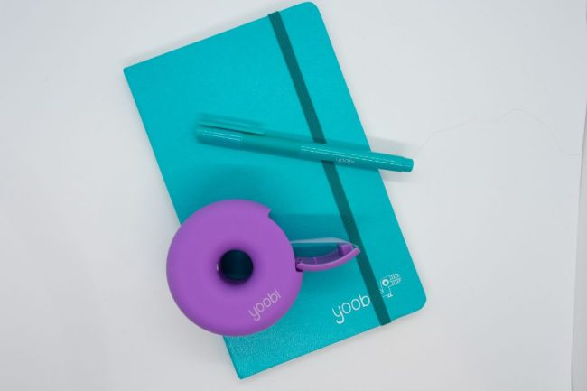 Purple circular tape dispenser and blue pen sitting on top of a blue notebook with a Yoobi Products logo