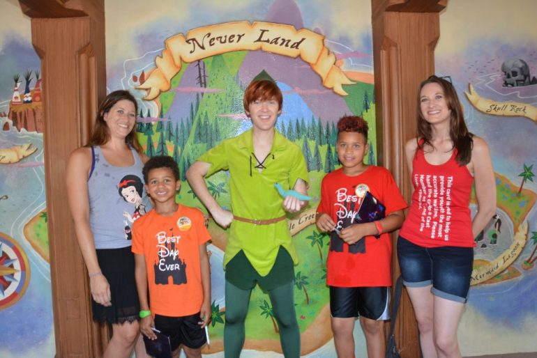 Theresa, her sister, and two nephews posing with Peter Pan in the middle in front of a Never Land mural.