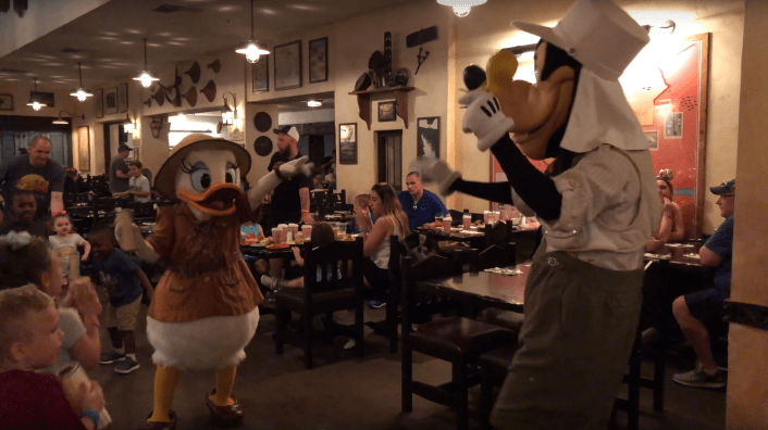 Daisy pointing at Goofy in Tusker House. surrounded by a group of children