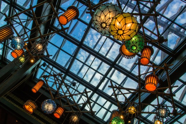 At Disney's Polynesian Resort, looking above the lobby you see blue skies and brightly colored light fixtures.