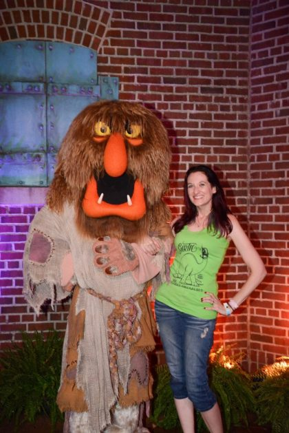 Theresa posing with Sweetums from The Muppets in front of a brick wall during DVC Moonlight Magic at Disney's Hollywood Studios