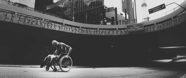 grayscale photo of man on wheelchair