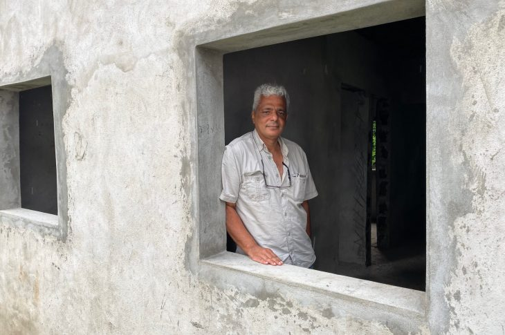 Walid Bahsoon in the window of the house he built using blocks made from plastic waste