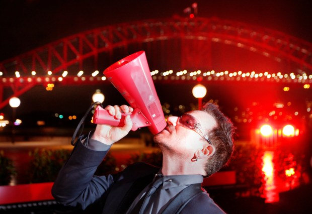 Bono poses for photographers in front of the Sydney Harbour Bridge at an event to launch World Aids Day