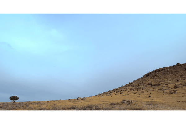 Clouds on an overcast day above a gently sloping high desert ground.
