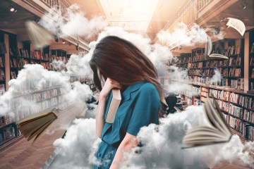 Woman in a library with books flying around her. She looks like she is stressed.