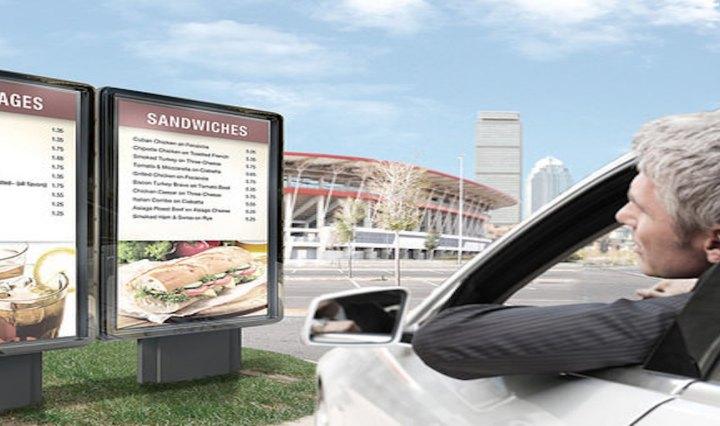 A guy in car looking at outdoor digital menu boards