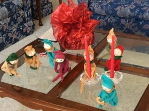 7 little cloth elves sitting on coffee table