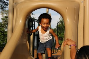 Laughing African American toddler on slide