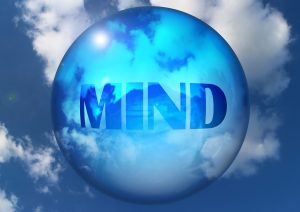 Mind written on transparent globe, sky & clouds in background