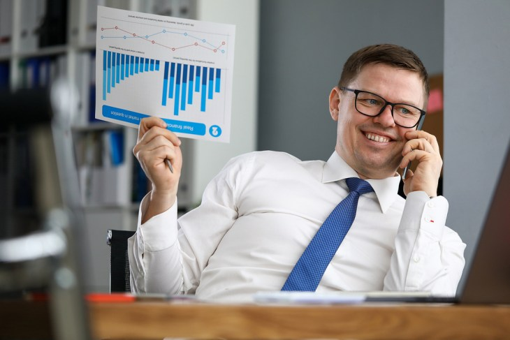 Smiling man talking on the phone while holding a document with charts.