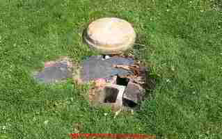 PHOTO of an unsafe septic tank cover placed over collpasing concrete blocks