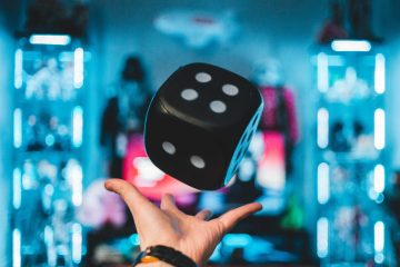 person's left palm about to catch black dice (unsplash.com)