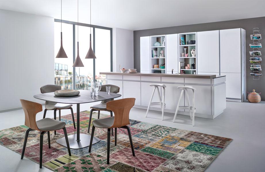 dans la piece a vivre l ilot cree la separation entre la partie cuisine et la partie salle a manger un tapis patchwork accueille l espace repas et