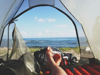 Man waking up inside a tent that overlooks a beach.